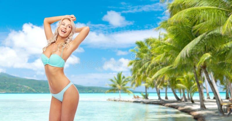Junge Frau, die im Bikini auf Strand aufwirft stockbilder
