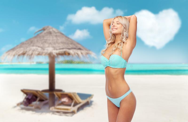 Junge Frau, die im Bikini auf Strand aufwirft lizenzfreie stockfotografie