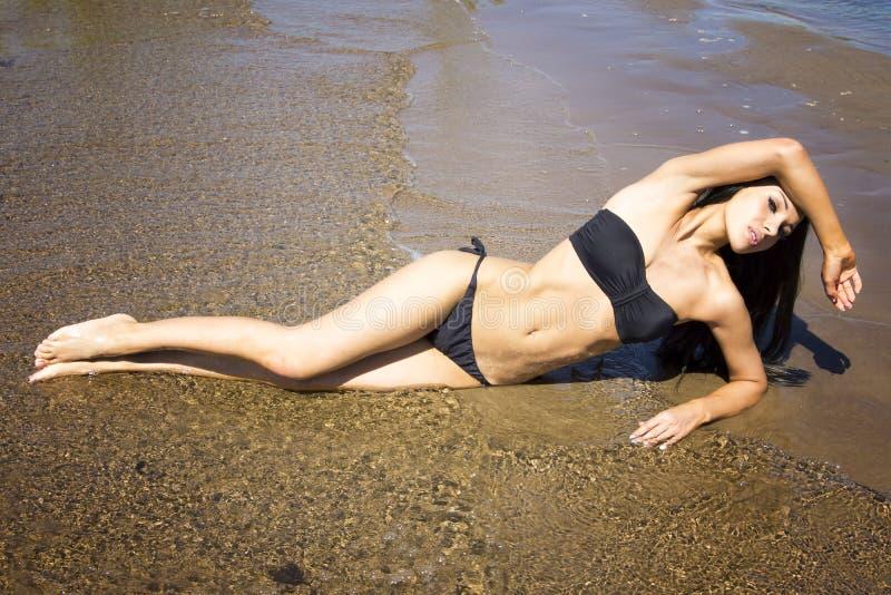 Junge Frau, die im Bikini ein Sonnenbad nimmt stockfoto