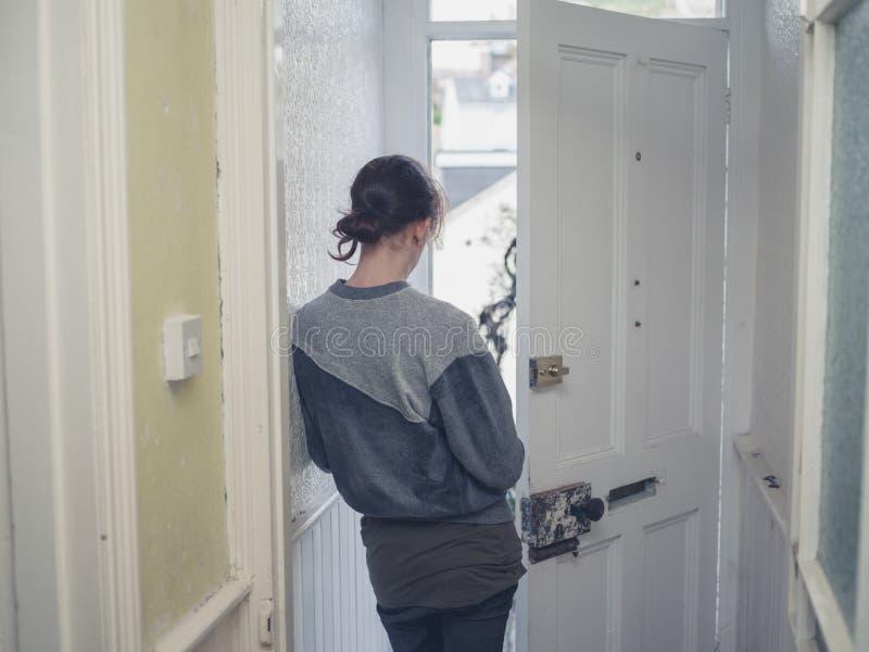 Junge Frau, die im Eingang steht lizenzfreie stockfotografie