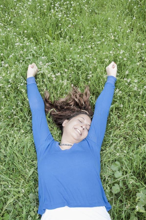 Junge Frau, die im Frühjahr auf Gras liegt lizenzfreie stockfotografie