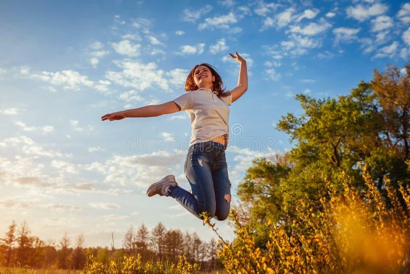 Junge Frau, die im Frühjahr Feld des Spaßes bei Sonnenuntergang springt und hat Glückliches und freies Mädchen genießt Natur lizenzfreies stockfoto