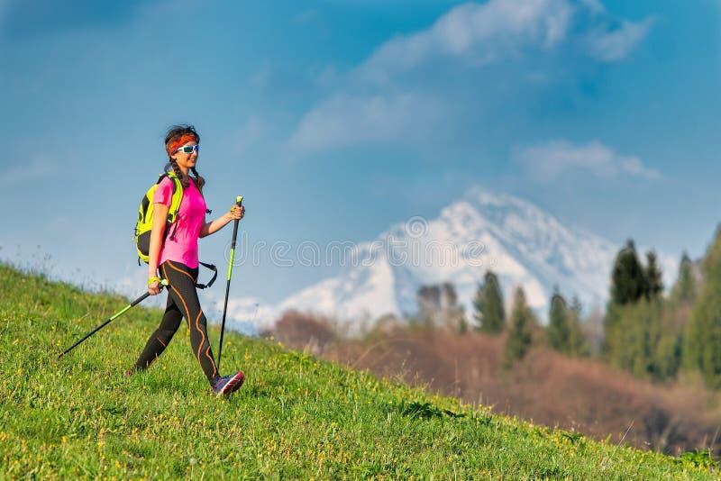 Junge Frau, die im Frühjahr von einer nordischen gehenden Exkursion in den Bergen zurückkommt lizenzfreie stockfotografie
