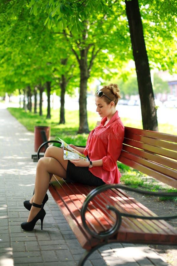 Junge Frau, die im grünen Park, Zeitschrift lesend sitzt stockfoto