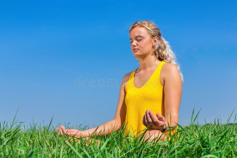 Junge Frau, die im Gras mit blauem Himmel meditiert lizenzfreie stockfotografie