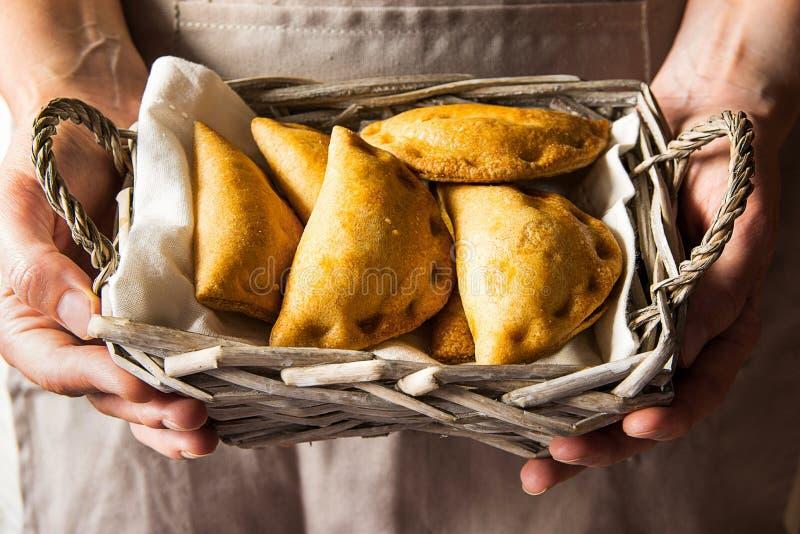 Junge Frau, die im Handweidenkorb mit frisch gebackenen empanadas Umsatztorten mit Gemüse Kinfolk hält stockbilder
