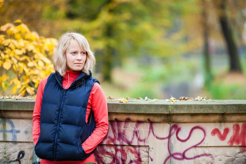 Junge Frau, die im Herbstpark sich entspannt stockfoto