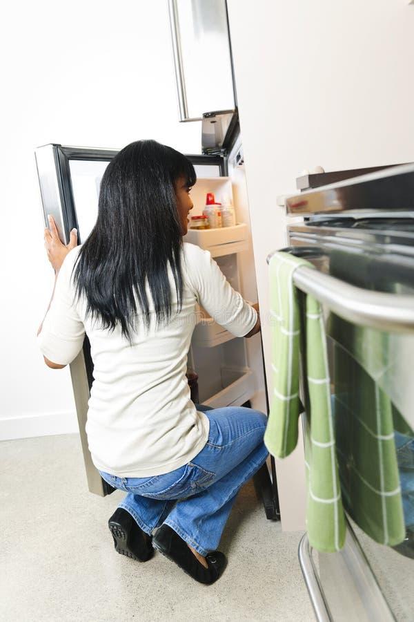 Junge Frau, die im Kühlraum schaut stockfotografie