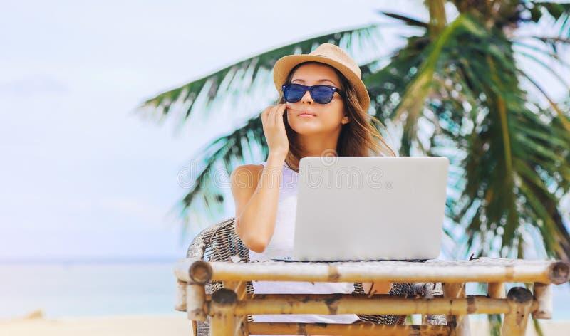 Junge Frau, die im Laptop auf dem Strand arbeitet Freiberufliche Tätigkeit lizenzfreie stockfotos