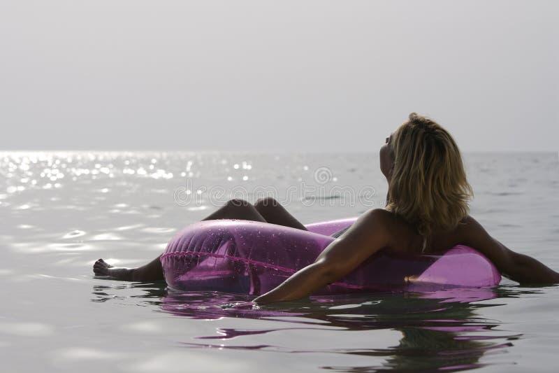 Junge Frau, die im Meer sich entspannt. lizenzfreie stockfotos
