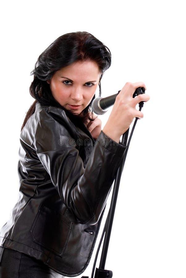 Junge Frau, die im Mikrofon singt stockfotografie