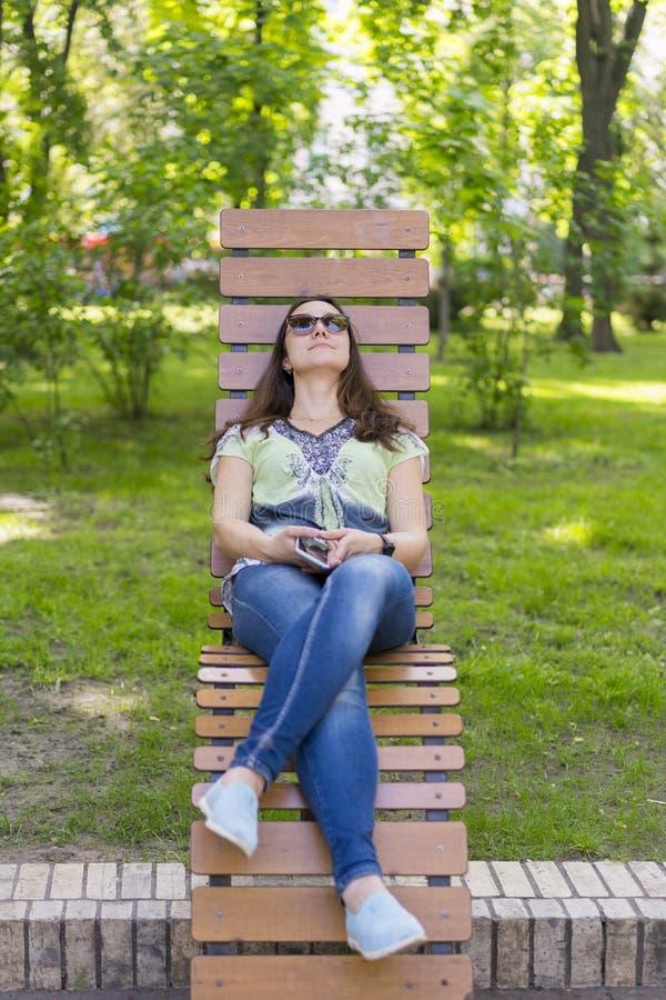 Junge Frau, die im Park auf der Bank stillsteht Schöne weibliche Entspannung auf einer Parkbank lizenzfreies stockfoto