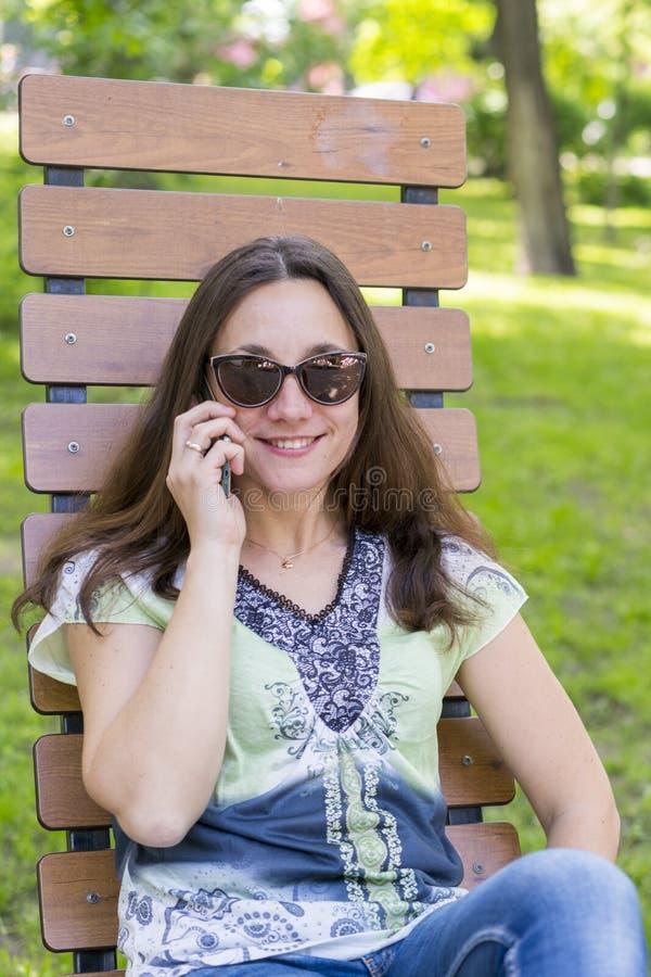 Junge Frau, die im Park auf der Bank stillsteht Sch?ne weibliche Entspannung auf einer Parkbank und Anwendung eines Smartphone ge lizenzfreies stockbild