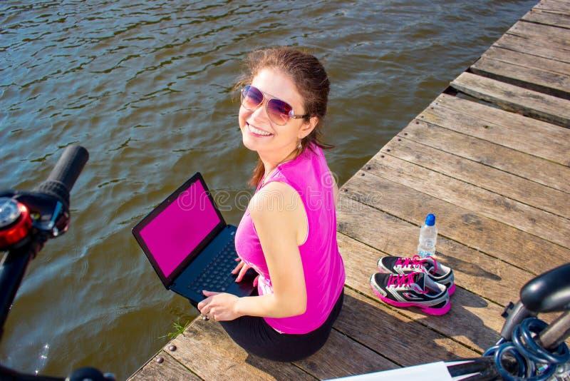 Junge Frau, die im rosa Hemd sitzt auf der Seebrücke unter Verwendung der Laptop-Computers trägt lizenzfreie stockfotos