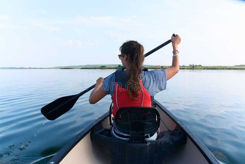 Junge Frau, die im See an einem Sommertag canoeing ist stockfotografie
