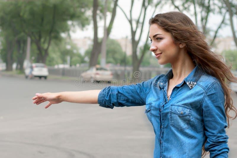 Junge Frau, die im sity per Anhalter fährt stockfoto