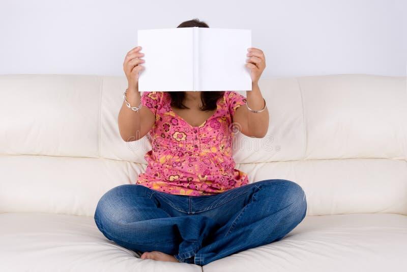 Junge Frau, die im Sofa liest weißes Buch sitzt lizenzfreie stockfotos
