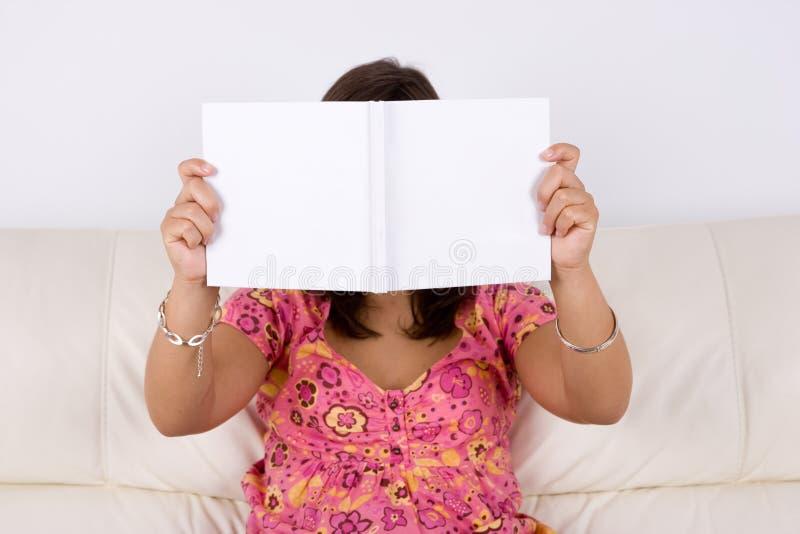Junge Frau, die im Sofa liest weißes Buch sitzt stockfoto