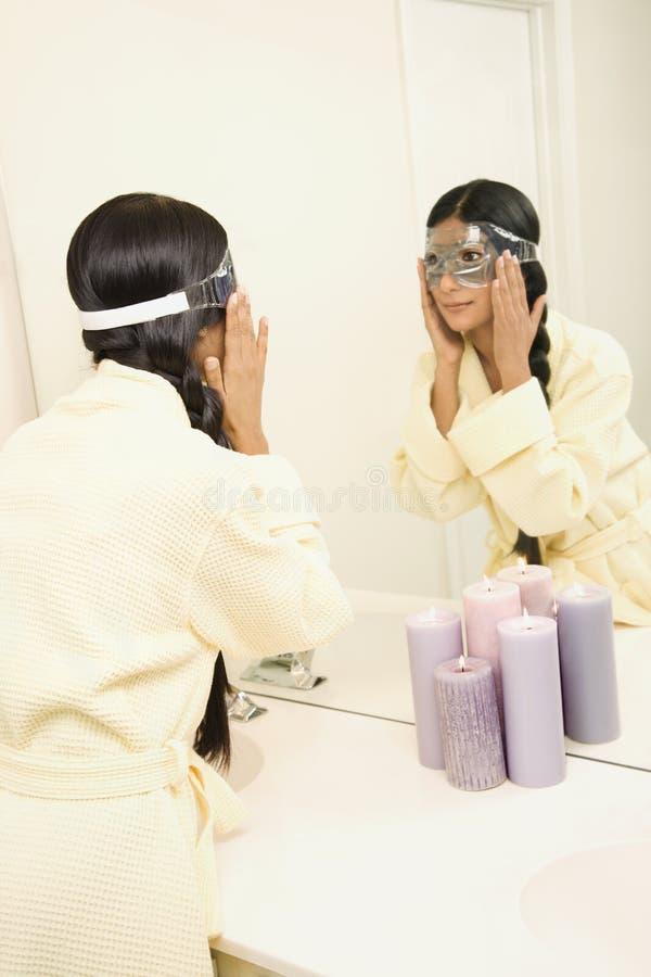 Junge Frau, die im Spiegel schaut. stockbilder