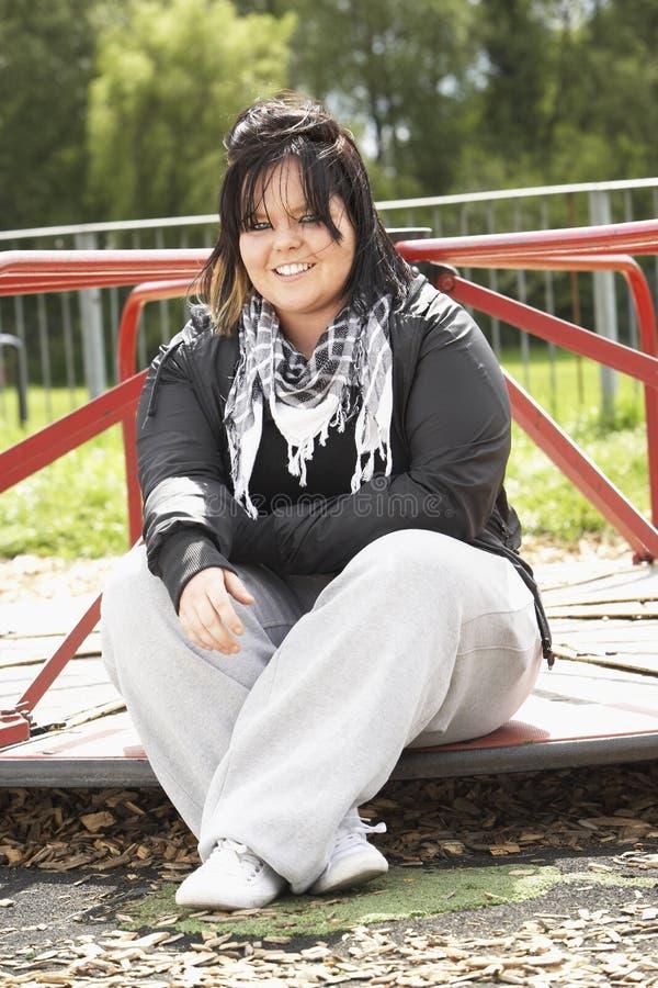 Junge Frau, die im Spielplatz sitzt stockbild