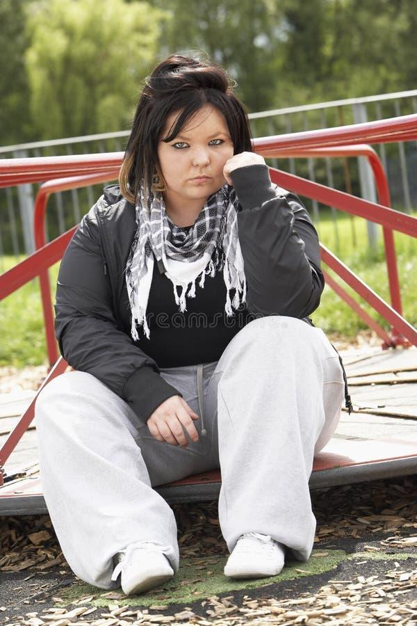 Junge Frau, die im Spielplatz sitzt lizenzfreie stockfotos