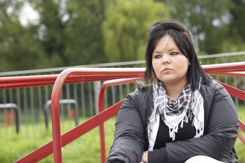 Junge Frau, die im Spielplatz sitzt lizenzfreie stockbilder