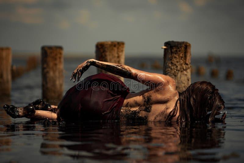 Junge Frau, die im therapeutischen Wasser von Schlammmündung badet stockfoto