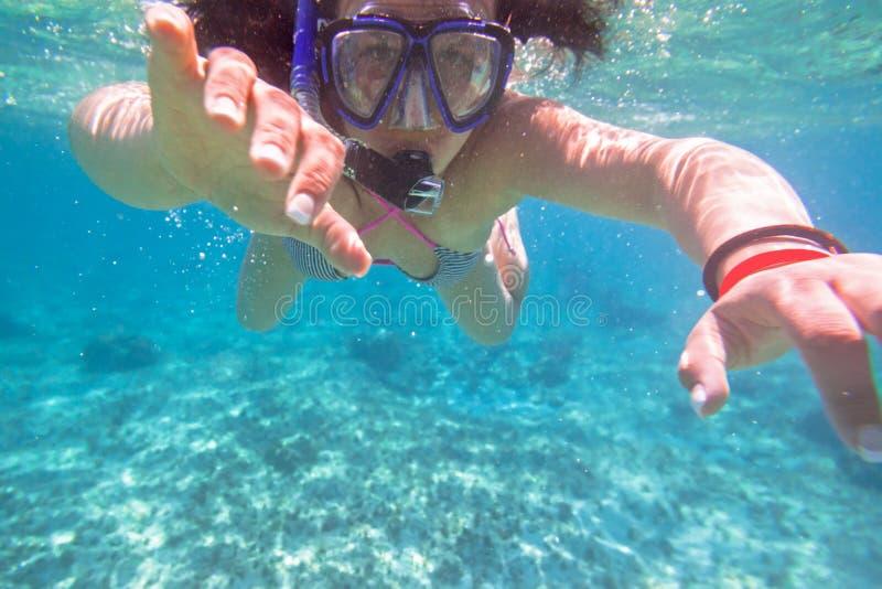 Junge Frau, die im tropischen Wasser schnorchelt lizenzfreie stockfotos