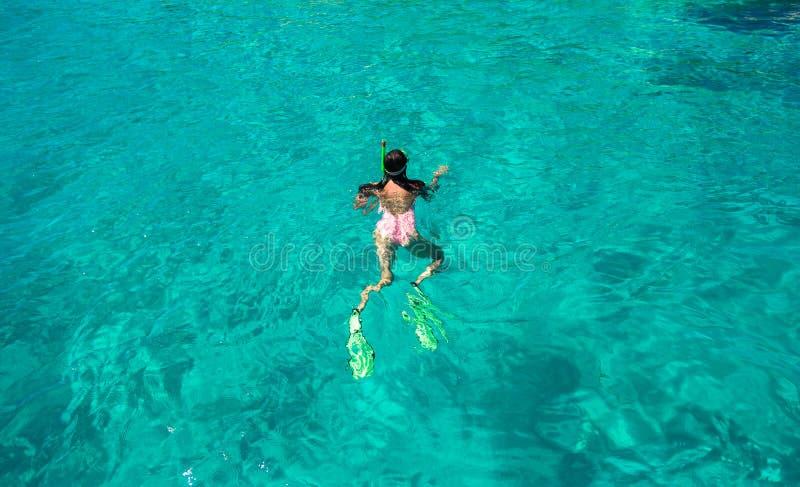 Junge Frau, die an im tropischen Wasser schnorchelt lizenzfreies stockbild