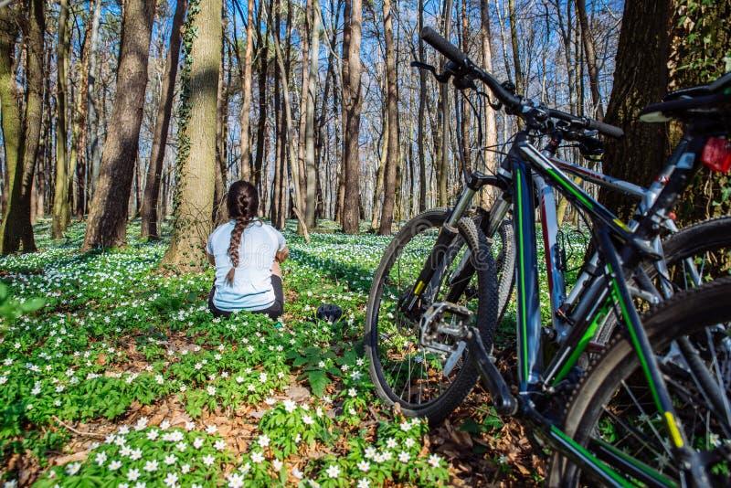 Junge Frau, die im Wald in der Mitte blühenden weißen Floridas stillsteht lizenzfreie stockfotografie