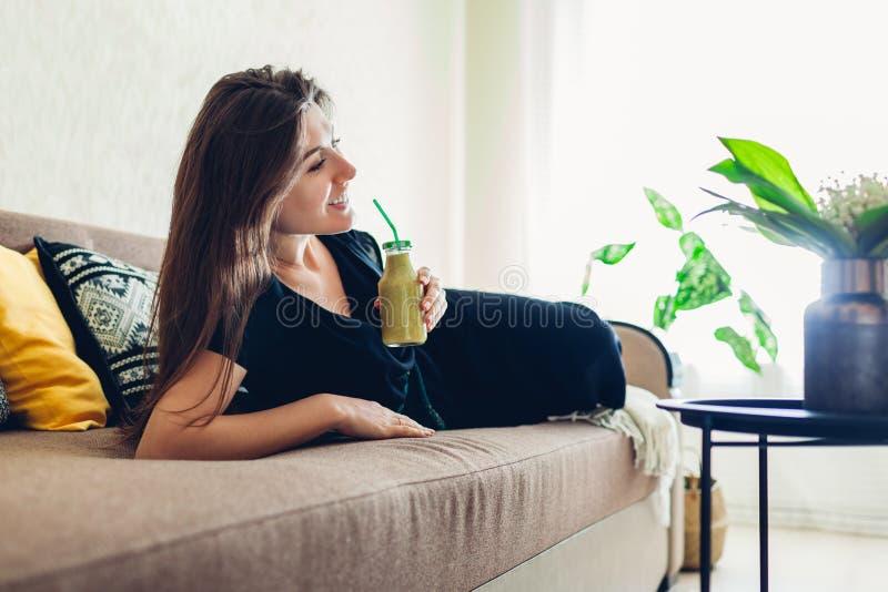 Junge Frau, die im Wohnzimmer und in trinkendem Smoothie sich entspannt Gesunde Di?t lizenzfreie stockfotografie