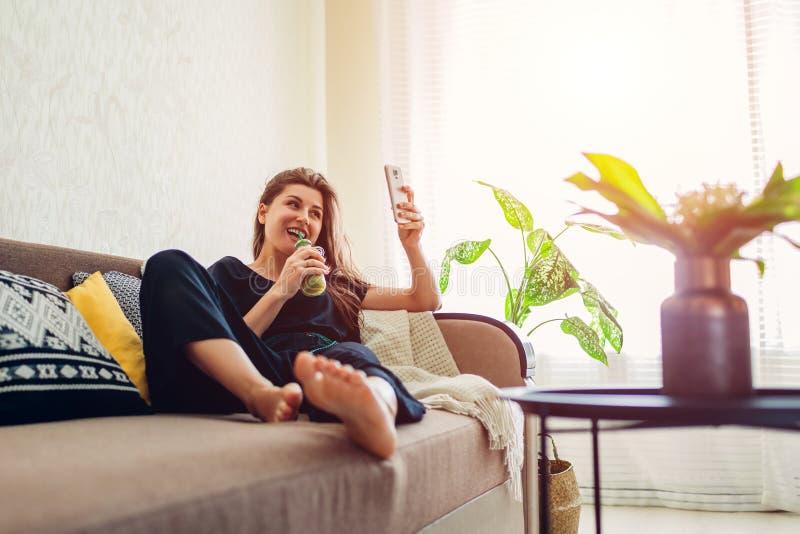 Junge Frau, die im Wohnzimmer und in trinkendem Smoothie unter Verwendung des Smartphone sich entspannt Gesunde Di?t lizenzfreie stockfotografie