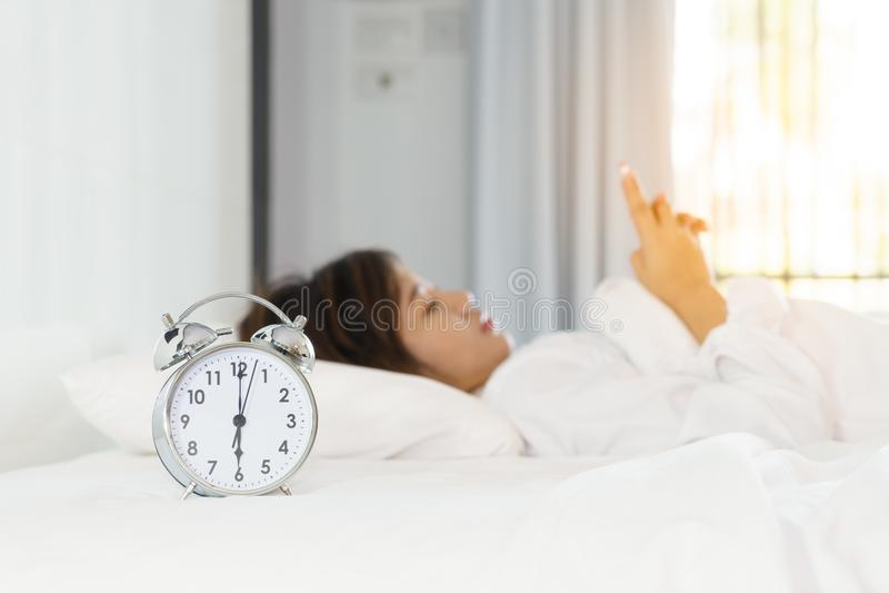 Junge Frau, die intelligentes Telefon auf Bett beim Aufwachen im morni verwendet stockfoto