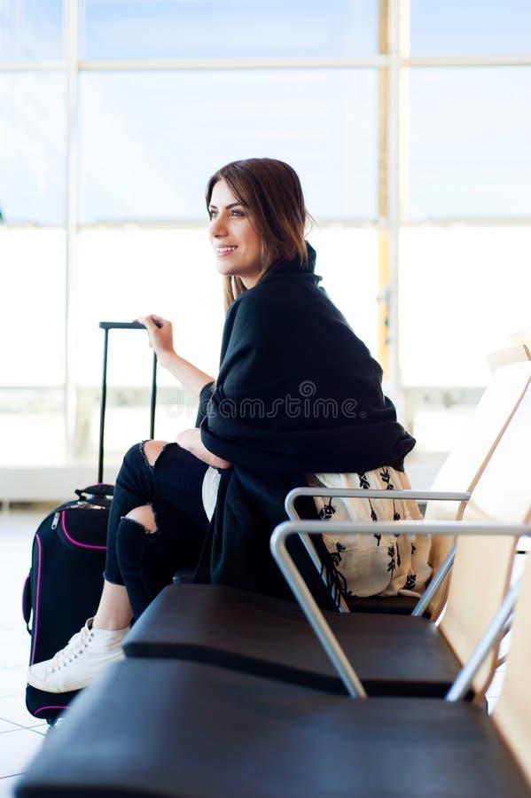Junge Frau, die in internationalen Flughafen wartet lizenzfreie stockbilder