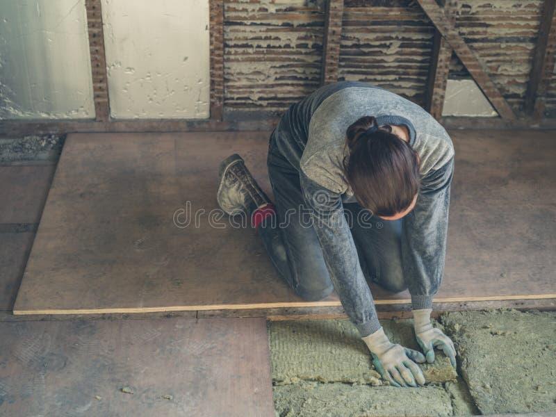 Junge Frau, die Isolierung im Dachboden legt stockfoto