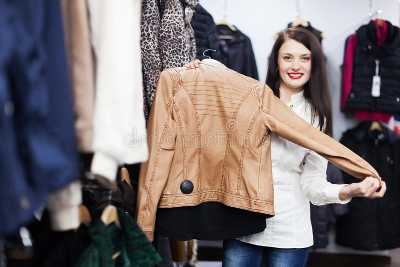 Junge Frau, die Jacke wählt lizenzfreie stockfotografie