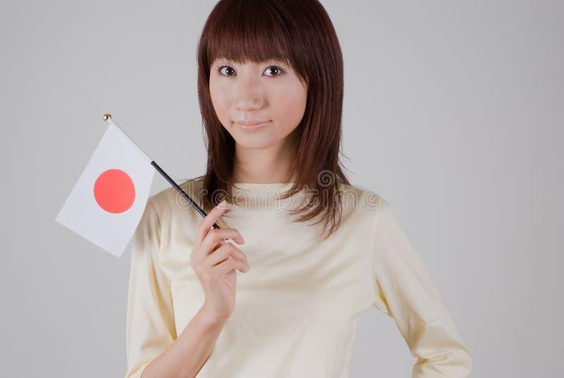 Junge Frau, die japanische Markierungsfahne anhält lizenzfreie stockbilder