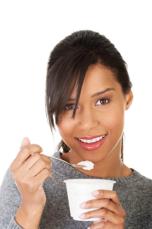 Junge Frau, die Jogurt als gesundes Frühstück oder Snack isst. stockfotografie