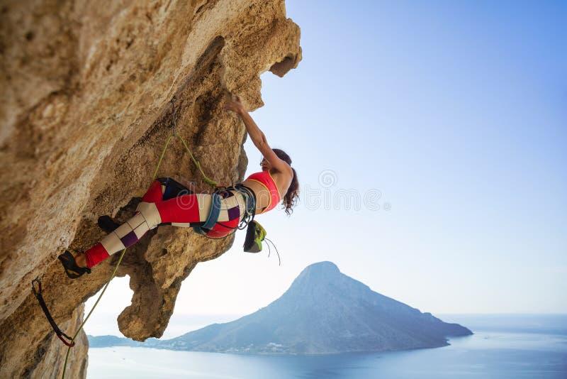 Junge Frau, die kämpft, um überhängende Klippe zu klettern lizenzfreie stockfotos