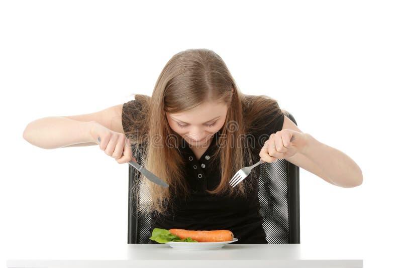 Junge Frau, die Karotte isst stockfotos