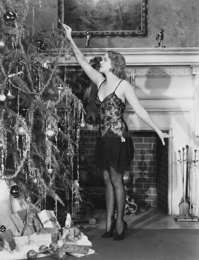 Junge Frau, die Kerzen auf Weihnachtsbaum beleuchtet (alle dargestellten Personen sind nicht längeres lebendes und kein Zustand e lizenzfreie stockfotografie