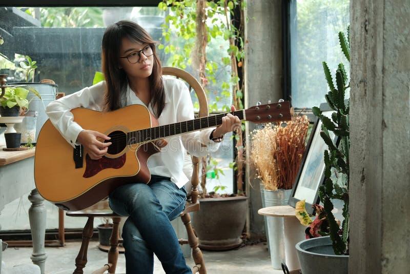 Junge Frau, die klassische Gitarre für das Spielen der Musik akustisch verwendet und lizenzfreies stockfoto