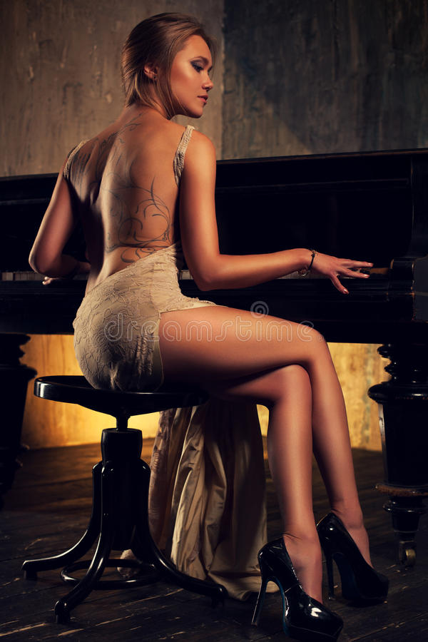 Junge Frau, die Klavier spielt lizenzfreies stockfoto