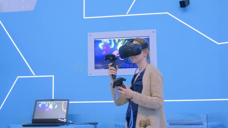 Junge Frau, die Kopfhörer der virtuellen Realität verwendet und mit speziellem Steuerknüppel zeichnet stockfotografie