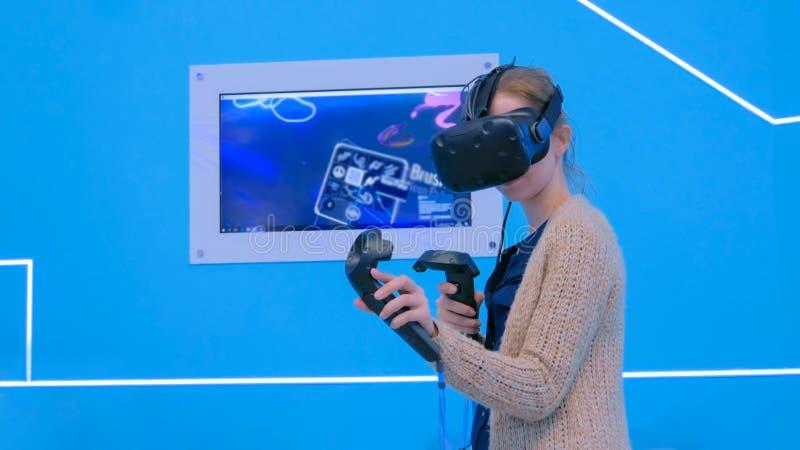 Junge Frau, die Kopfh?rer der virtuellen Realit?t verwendet und mit speziellem Steuerkn?ppel zeichnet lizenzfreie stockfotos