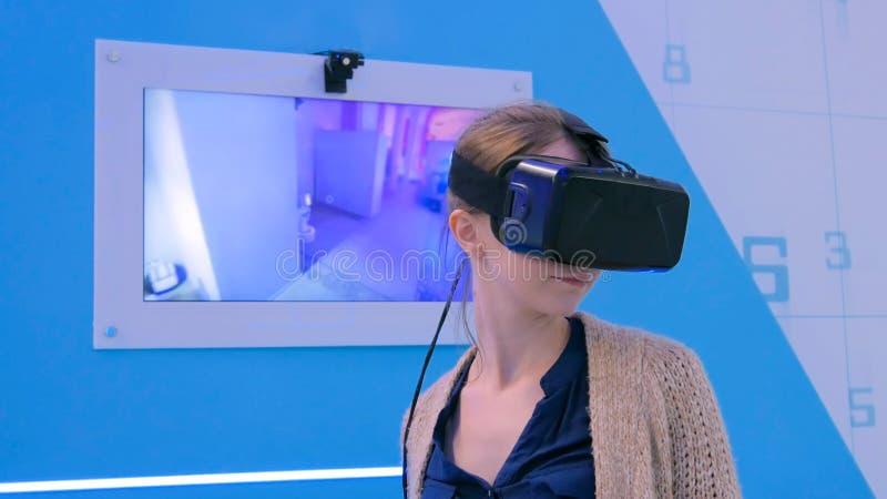 Junge Frau, die Kopfh?rer der virtuellen Realit?t verwendet stockfotos