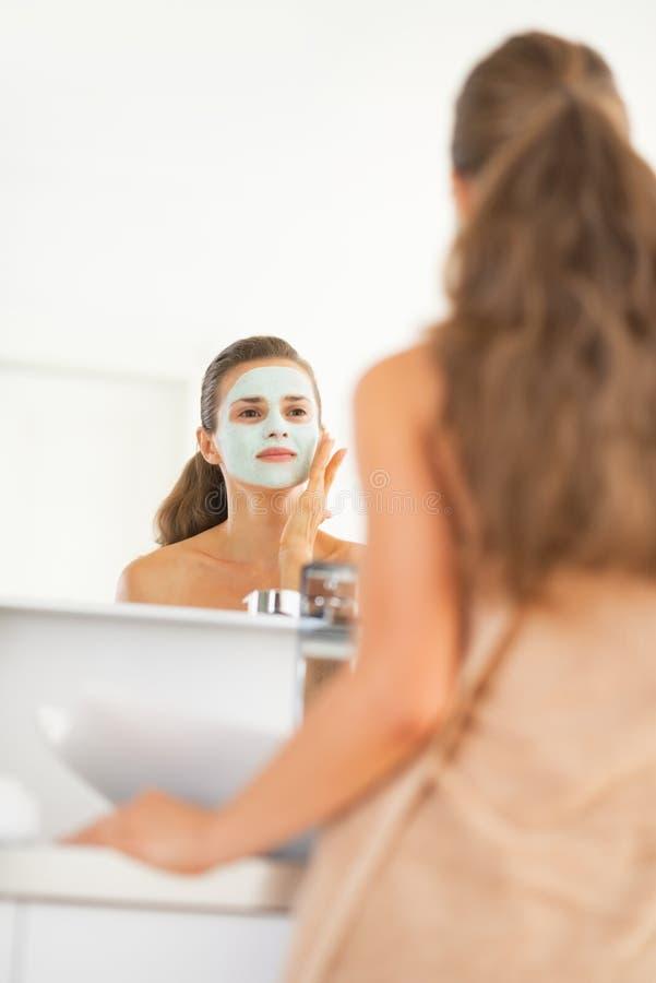 Junge Frau, die kosmetische im Gesichtmaske trägt lizenzfreie stockbilder