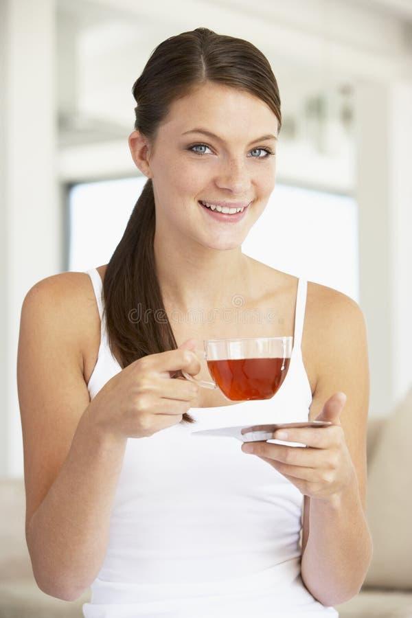 Junge Frau, die Kräutertee trinkt stockbilder