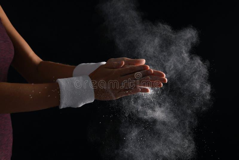 Junge Frau, die Kreidepulver auf Händen anwendet lizenzfreie stockbilder