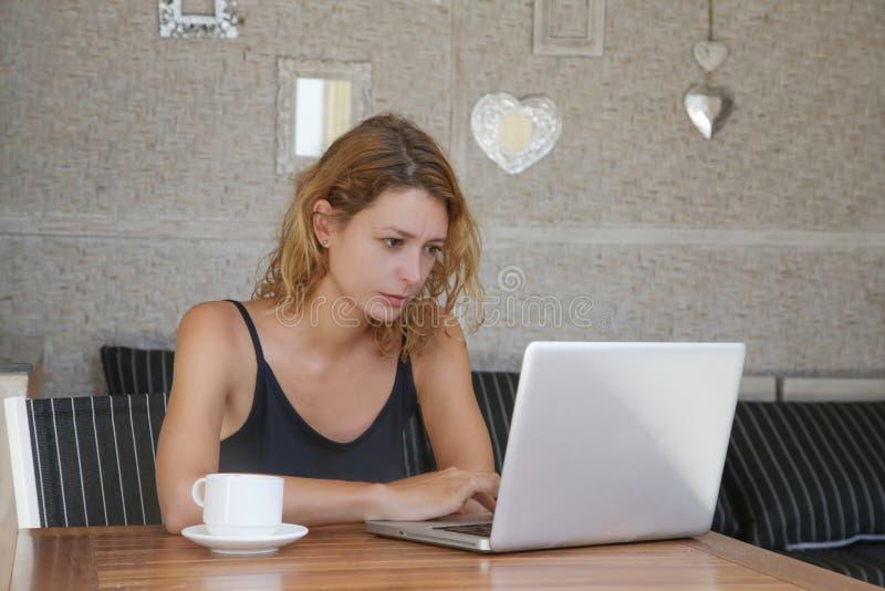 Junge Frau, die Laptop beim Trinken des Kaffees verwendet lizenzfreies stockfoto